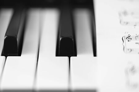 Classic piano and musical sheet . Black and white photo, Musical Background