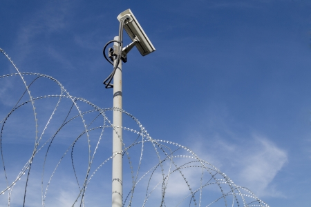 Security camera and barbed wire against blue sky Stock Photo - 17594368