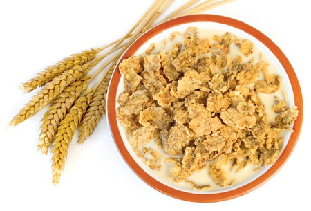 Bowl with corn flakes and wheat on the white background Stock Photo