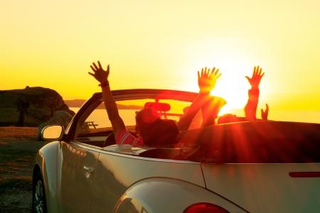 cabrio: Gelukkig gezin in een auto tijdens zonsondergang in de zomer