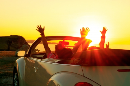 convertible car: Happy family  in a car during sunset in summer