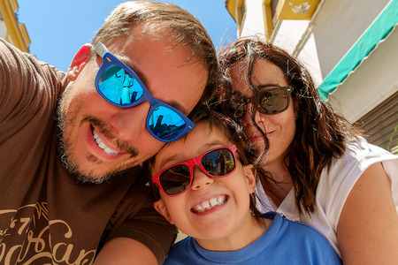 Family having fun wearing sunglasses   waving to a camera taking selfie photograph on summer holiday Stock Photo