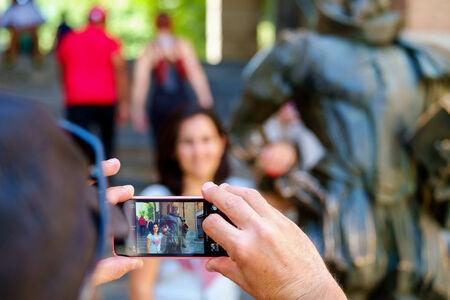 Bir cep akıllı telefon ile bir kadının resmini alarak bir adam Stock Photo