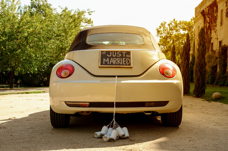 feleségül: Esküvői autó házasok jel egy táblára és kannák csatlakoztatva