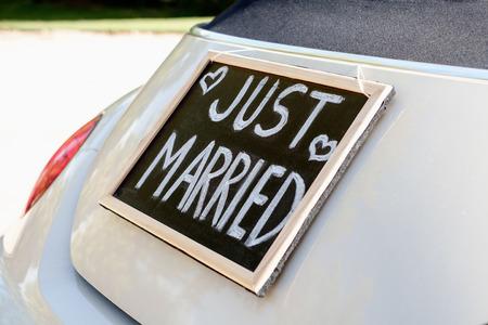 net getrouwd: Bruiloft auto met net getrouwd teken in een schoolbord