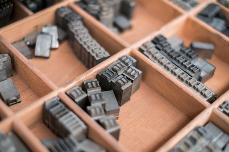 printery: A wooden box containing type script letters - Typography