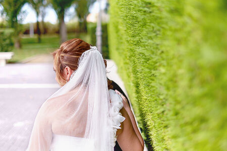 A bride outdoors with her veil, soft focus