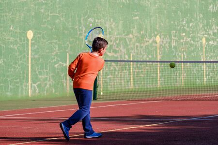 Young boy playing tennis on a court
