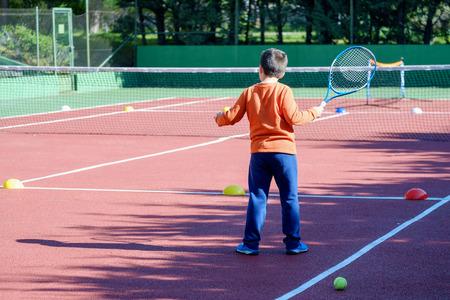 TENIS: Muchacho joven que juega al tenis en una cancha Foto de archivo