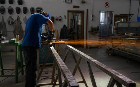 A worker inside factory using blowtorch