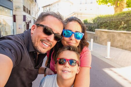 guy portrait: Family having fun wearing sunglasses & waving to a camera taking selfie photograph on summer holiday