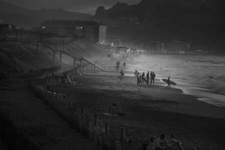 Beautiful panoramic night scene of a beach with surfers, in black and white Stock Photo