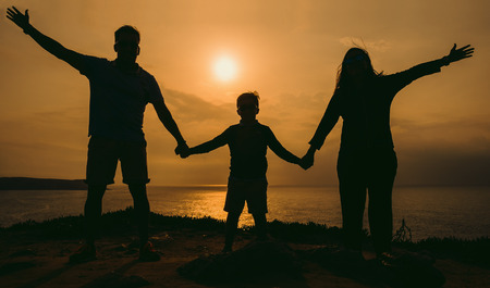 Silhouette, happy children with mother and father, family at sunset on a summer day