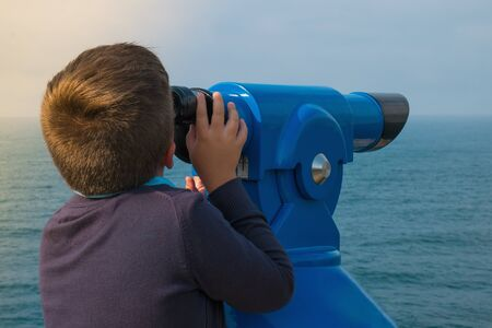 A boy looking through sightseeing binoculars tourist telescope overlooking the ocean landscape
