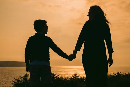 Mother and son on sunset holding by hands, outside isolated in front of a sunset in the sky on a summer day Stock Photo