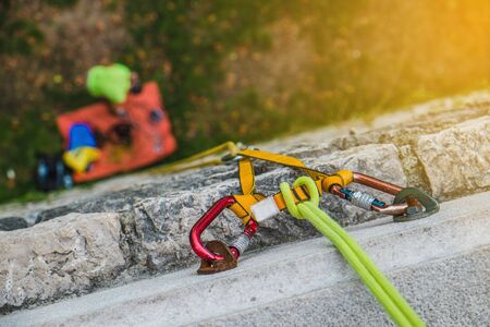 Close-up of a rock climbing rope with hooks on rock at sunset