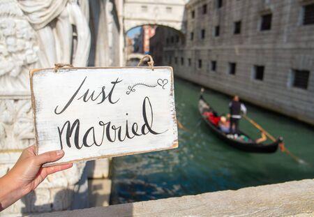 recien casados: Romántico signo Sólo se casó en el canal en Venecia Foto de archivo
