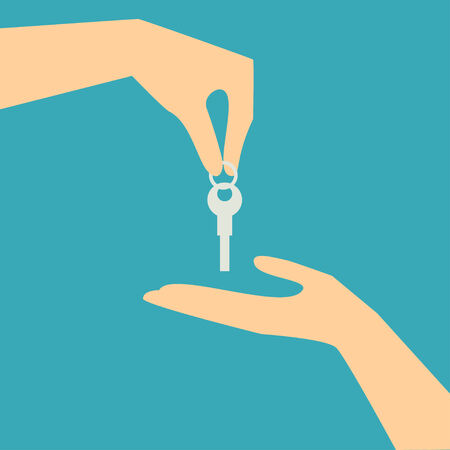 hand and key: Concept illustration of buying and selling house in real estate market  The hand holding the key chain is the seller or the owner and the arm receiving the house key is the buyer or purchaser