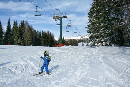 Bébé en salopette bleue skier sur une piste de ski sous le siège. Les cabines pour les skieurs ci-dessus. Val di Fiemme, en Italie.