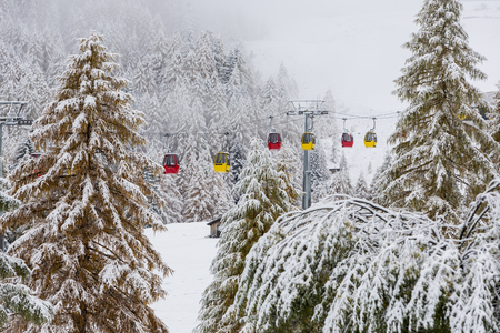 top down car: Snowy forest and colorful gondola cabins, Dolomites, Italy.