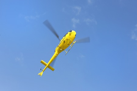 helicopter rescue: Helicopter rescue, Yellow helicopter in the air while flying on blue sky, bottom view. Stock Photo