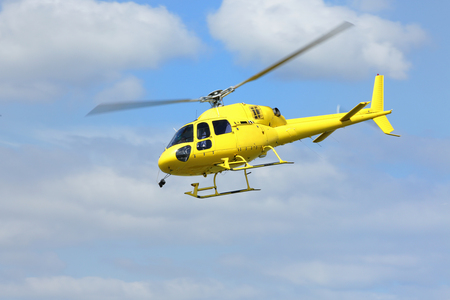 Hubschrauberbergung, Gelb Hubschrauber in der Luft während des Fluges auf blauem Himmel. Standard-Bild