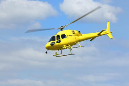 Hubschrauberrettung, gelber Hubschrauber in der Luft beim Fliegen auf blauen Himmel.