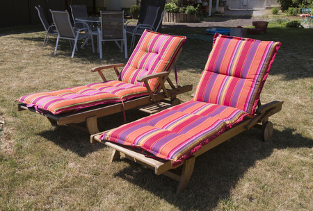 Two lawn chairs on the sun-drenched garden with colorful covers..