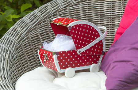 nursing mother: Little red doll buggy on a chair.