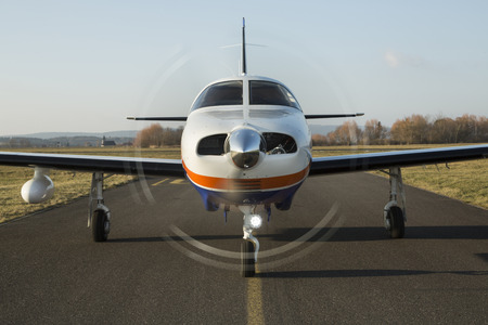 piper: Small private single-engine piston aircraft on runway, front view