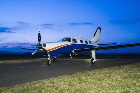 Petit avion privé à piston mono-moteur sur la piste au coucher du soleil Banque d'images