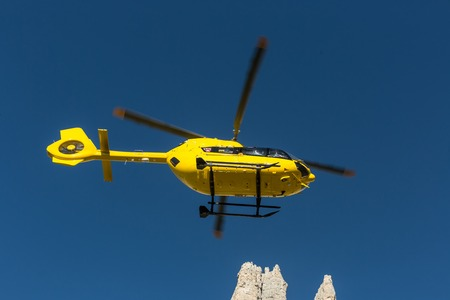 helicopter rescue: Yellow helicopter used for rescue operations, On the ground in Dolomites, Italy. Helicopter rescue. Medical rescue helicopter flying rescue injured climber on the Tre Cime. Italy, Dolomites