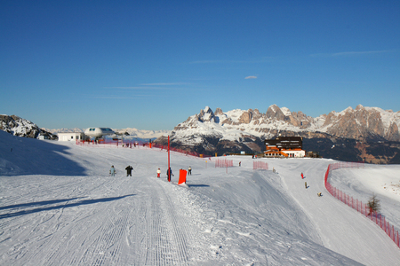 Adjusted slope on the mountain top. Skiing on the dolomites, Val di Fiemme, Italy.