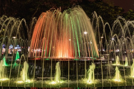 colorfully: Colored fountain at might in circle inn Hai Phong, Vietnam. Brightly and colorfully lit fountain
