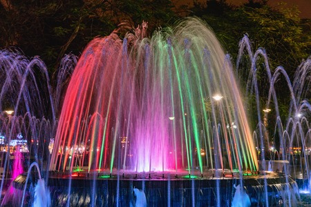 Colored fountain at might in circle inn Hai Phong, Vietnam. Brightly and colorfully lit fountain