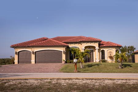 Typisch betonblok uit Zuidwest-Florida en stucwerk op het platteland met palmbomen, tropische planten en bloemen, grasvelden en pijnbomen. Florida. Zuid-Florida eengezinswoning