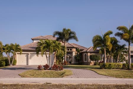 Bloc de béton typique du sud-ouest de la Floride et stuc à la campagne avec des palmiers, des plantes et des fleurs tropicales, des pelouses et des pins. Floride. Maison unifamiliale du sud de la Floride