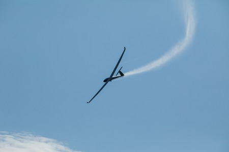 The glider flying in the blue sky drains the water from the wings before landing.