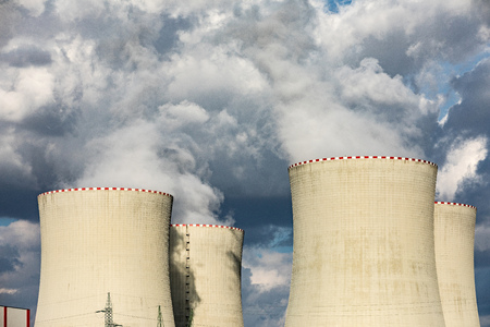 Nuclear power plant in dusk landscape with big chimneys