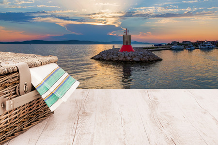 picnic basket and table on the harbor in summer evening picnic table Zdjęcie Seryjne - 83761760