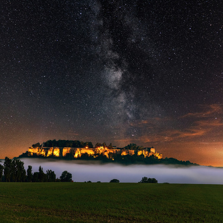 Night view of the Milky Way above the illuminated Koenigstein Fortress. The enlightened Konigstein fortress and the fog in the Elbe Valley. castle Konigstein Germany. Saxon Switzerland.