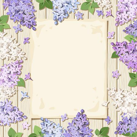 ejemplo de una hoja de papel y flores de color lila morado, blanco y azul sobre un fondo de madera.