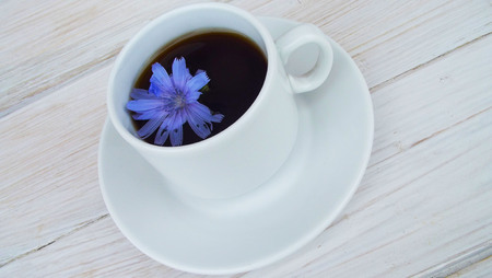 Delicious and healthy beverage from chicory, on wooden background.