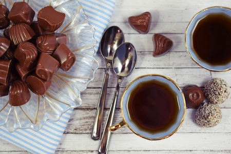 Fresh flavored tea and chocolates on wooden background.