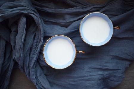 Milk with a blue cup on a blue napkin. Standard-Bild - 122322151