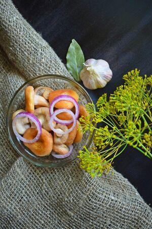Delicious marinated mushrooms with garlic and onions in a glass jar.