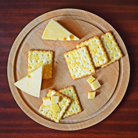 Fresh crispy cracker with cheese and sesame on wooden background.