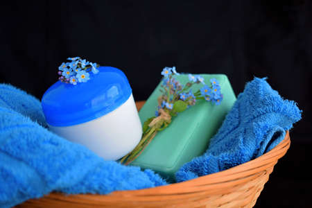 Cosmetic soap and cream with a light floral scent on a blue towel in a wicker basket.Blue forget me nots.