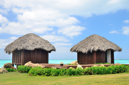 bungalows: Two bungalows in front of turquoise sea. Stock Photo