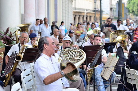 A musician with a french horn in an orchestra.
